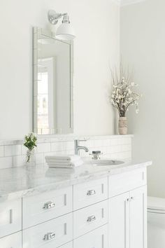 Chic, white bathroom features a white washstand adorned with polished nickel vintage cup pulls topped with white marble fitted with a round sink and modern faucet accented with a subway tiled backsplash with a marble ledge placed under a mirror tile mirror.