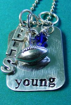 Necklace comes with players name and school colored crystal and 3 school letter charm and silver football.
