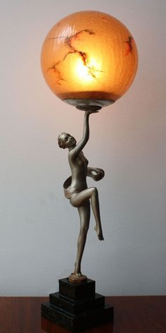 "Art deco spelter figure lamp, circa 1930, in the style of a Lorenzl ""scarf dancer"". The muted silver colour cold-painted spelter figure mounted on a 3 tier marble base holding aloft a beautiful original ""marbled"" glass globe-58cm H. Beautiful art deco spelter lamp, with great style and lovely slim lines in the manner of Lorenzl. (hva)"