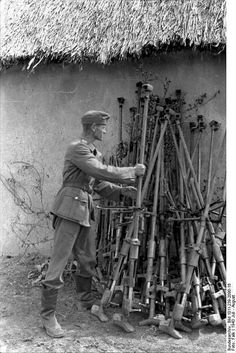 """A German soldier collects Russian PTRD-41 (Protivotankovoye ruzhyo Degtyaryova, """"Degtyaryov Antitank rifle"""") rifles after the end of battle. The PTRD-41 was a produced and used from early 1941 by the Red Army. It was a single-shot weapon which fired a 14.5x114mm round. Although unable to penetrate the frontal armor of German tanks, it could penetrate the thinner sides of early-war German tanks as well as thinly armored self-propelled guns and enemy bunkers. (July-August 1943)"""