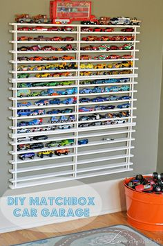 DIY Matchbox Car Garage  I'm in love.  Not only was this crazy easy to make (minus the mistake of hand painting it), cheap and functional but it's also super cute to look at!  It's almost like a piece of art on the wall.  The boys love it, too.  It's like their own little car museum.  And now they can easily find and access the car they are looking for instead of dumping the basket of cars all over the floor!