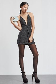 The Bourbon Dress is a metallic novelty knit micro mini dress with a plunging neckline and knotted detail at the waist.