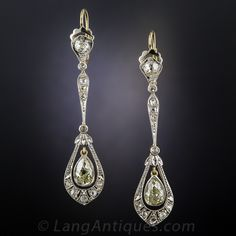 Edwardian Long  Diamond Drop Earrings. Over 2 inches long and exceptionally lovely Edwardian diamond ear drops dating from the early twentieth century. These slender, chic and sexy sparklers highlight a pair of antique pear shape diamonds, weighing just under a carat each, freely swinging inside shapely frames of platinum over 18K gold, glittering with tiny rose-cut diamonds...