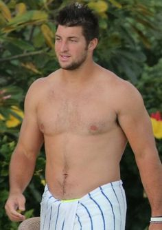 Tim Tebow shows off his shirtless muscular physique while on vacation in Hawaii over the weekend. The football player was seen spending time withamp;