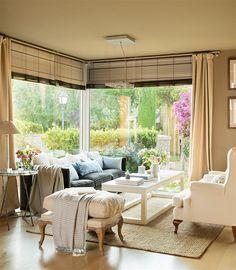 Salón con paredes y techo en color beige rodeado de jardín