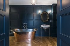 Luxurious en suite bathroom with navy blue walls, wooden flooring, and a gorgeous copper bath. Copper Tub, Copper Bathroom, Modern Bathroom, New Kitchen Doors, Paint For Kitchen Walls, Bathroom Sinks For Sale, Bathroom Renovations, Bathroom Ideas, Bathroom Designs