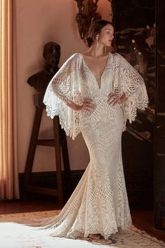 Made from intricate graphic lace, this fitted gown features a plunging v-neckline and dramatic train. The cascading flutter sleeves transform into a gorgeous cape detail to frame the open back. Bridal Outfits, Bridal Dresses, Mexican Wedding Dresses, Spanish Lace Wedding Dress, Cotillion Dresses, Garden Wedding Dresses, Peplum Wedding Dress, Gatsby Wedding Dress, Hollywood Glamour Wedding