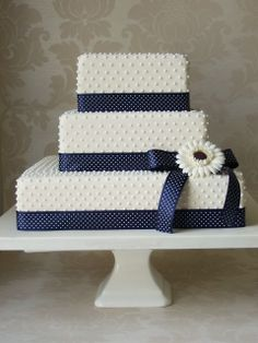 ivory, dots, navy blue polka dot wedding cake with ribbon & flower.