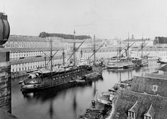 Colbert (French Battleship, 1875), left center, and Redoutable (French Battleship, 1876), right center. Moored off Brest navy yard, France circa the late 1870s or early 1880s. The two battleships are as first completed, with ship rigs. An armored cruiser of the Victorieuse class is moored off Colbert's port side, with only its lower masts in place. A coast defense ship (probably Tempéte) is moored off Redoutable's port side. Note the docky...