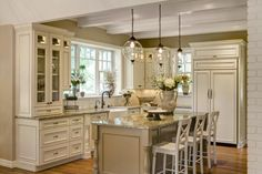 It's the small details that give this kitchen a personal touch. White Ceiling beams, white cabinetry and stunning pendant lights come together to create a bright, open space.