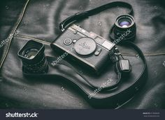 Leica M6 and lens/Image of a black Leica M6 camera body with a Summicron 35 mm and a Summarit 50 mm lenses sitting on a black leather surface. Bucharest, Romania, May 6, 2016.