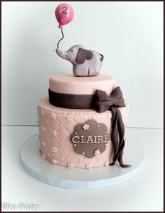A pink and grey elephant themed cake with balloon, bow and flowers.