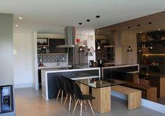 Cozinha integrada. Legal a ideia do espelho que ajuda a dar impressão de espaço e das cadeiras e banco na mesa.