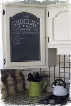 Chalkboard in the kitchen~ Three coats of Rustoleum's black chalkboard paint, applied to Masonite with a foam roller, which is temporally set into the recessed panel of the cabinet door.  SO CUTE.