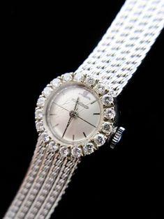 Salle de ventes ABC : Joaillerie JEAGER LE COULTRE, montre de dame en or blanc 18 carats à mouvement mécanique, cadran à chiffres batons dans un entourage de 13 diamants taille brillant pour 0,52 carats