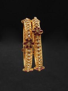 Golden bangles with red floral design
