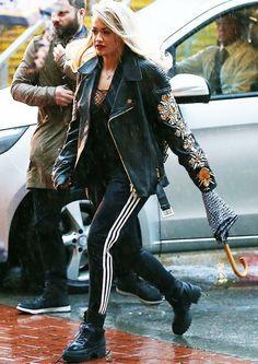 Rita Ora wears an embellished oversize moto jacket, black top, Adidas pants, and combat boots