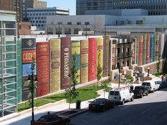 """Kansas' City Public Library Giant Bookshelf in Kansas City, Missouri, USA. The Central Library Parking Garage, """"The Community Bookshelf,"""" showcases 22 book spines and titles that were suggested by Kansas City readers. Kansas City Library, Central Library, Beautiful Library, Book Wall, Lectures, Library Books, Library Memes, Library Wall, Main Library"""