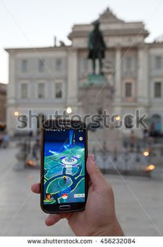 PIRAN, SLOVENIA - JULY 19, 2016: Photo showing a smart phone and a hand of a person playing a Pokemon Go game nearby the statue of composer Tartini. Location features a Pokemon gym.