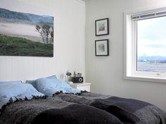 Det skulle være enkelt å drømme søtt i dette soveromsmiljøet. Bildet på veggene er tatt av eieren selv, og er derfor unikt. Legg merke til at utsikten harmonerer perfekt med bildet og fargene på pleddet.