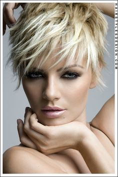 Hair Style: This is a pixie hairstyle that looks really sexy. This beautiful young woman has her hair short all around. The hair has been layered and brought forward on top and at the forehead. Bangs are styled onto the forehead for this chic look. Hair Cut: This haircut is short. Hair Colour: The hair colour is blonde.
