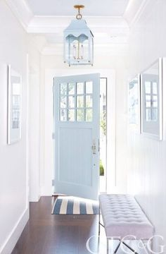 A coastal blue door invites guests into a clean classic foyer.