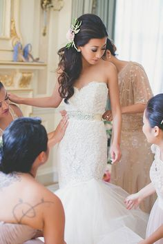 Intimate East-Meets-West Boston Wedding, Bride Getting Dressed in Strapless Gown | Brides.com | Photo: Katch Studios