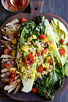 An EASY 15-minute grilled chicken dish you'll want to make all summer long! Fresh heads of romaine lettuce are split down the middle, grilled until slightly charred and smoky, along with fresh corn and skinless chicken thighs, then topped with tomatoes, onions, avocado and a simple salsa vinaigrette.