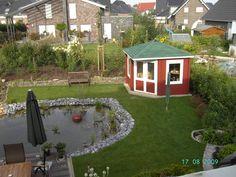 Ein schwedenrotes fünfeckiges Gartenhaus mit großen Fensterflächen blickt auf den mit Ziersteinen eingefassten Gartenteich.