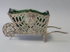 The firm of Christoph Widmann was founded in Pforzheim, Germany in 1919. They were known for creating high quality silver. This silver cart, fitted with a green glass liner, was made in the 835 standard, which is higher than the usual 800 standard used in Germany. It is possible that this piece was made for export, as were most of the pieces done in the 835 silver standard. The cart is beautifully cast with scrollwork and 4 heart shaped cartouches, 3 of which are repousse with figures.