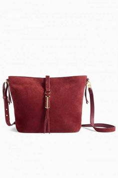 Italian suede in rich burgundy in a bucket-style bag with custom hardware. Our…