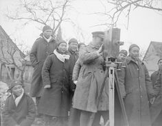 CHINESE NEW YEAR CELEBRATIONS FRANCE FEBRUARY 1918 (Q 10260)   Men of Chinese Labour Corps interested in the official cinematographer who is taking a record of New Year celebrations at the Labour Corps Camp at Noyelles, 11 February 1918.