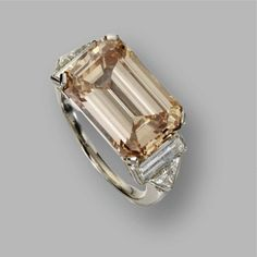Fancy orange-brown diamond ring. The emerald-cut diamond of fancy orange-brown color weighing 8.69 carats, flanked by 2 baguette and 2 triangular-shaped diamonds weighing approximately 1.60 carats, mounted in platinum.