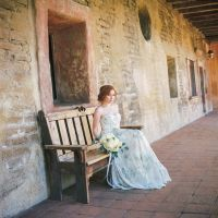 """We're bidding adios to summer in style with an estival bridal portrait shoot set at Mission San Juan Capistrano, a 241-year-old California landmark whose meandering grounds boast exotic gardens, bougainvillea-draped archways, bubbling fountains cloistered by weathered adobe walls, a four-bell campanario, and a series of exhibits that bring the Spanish colonial era—and California's multicultural heritage—to life. Often called the """"Jewel of the Missions,"""" the site is also home to the Serra…"""