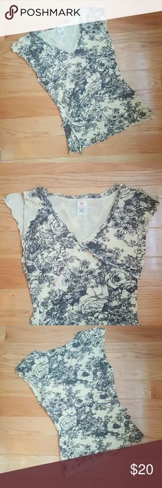 Anthro Floral Blouse Pretty black floral and beige top. V neckline, faux wrap front, split cap sleeves, ruching detail on side with decorative tie. Material has a mesh/nylon feel to it and is stretchy. Excellent pre-loved condition. Cross stitched heart for Anthropologie. Anthropologie Tops