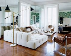 In the living area of Atwood's apartment, which was renovated by architect Matteo Bermani and decorated by Nate Berkus, a vintage Arredoluce Triennale floor lamp illuminates a sofa by Patricia Urquiola for B&B Italia; the 1970s cocktail table is from 1stdibs.com, and the vintage hand chair was found at a Manhattan antiques shop.   - ELLEDecor.com