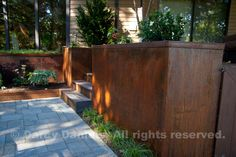 Built-in planter boxes made of Cor-ten steel are integrated into a flowing deck and patio layout. Garden Design: Darcy Daniels, Bloomtown Gardens. Landscape contractor: Tryon Creek Landscape.
