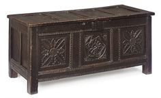 Elizabethan oak paneled chest with intricate carvings. Chest appears to be heavy and dense, characteristics of Elizabethan furniture.