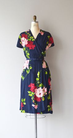 Vintage 1940s deep navy blue rayon dress with bold and vibrant rose and leaf print, wrap style bodice, navy belt, short sleeves, side drape and metal