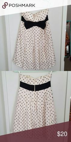 Super sweet strapless dress with bow! Super cute, cream colored with black polka does and the bow is attached all the way around the back to help give the appearance of a tiny waist! It has a zipper in the back. There are no straps. It was only worn once for a homecoming dance! Papaya Dresses Prom