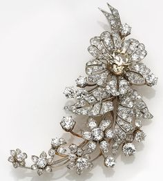 A late Victorian colored diamond, diamond and platinum-topped flower brooch  the brooch designed as a crescent shaped floral cascade featuring a light brown old European-cut diamond, remaining flowers and leaves set throughout with old European-cut diamonds; estimated center diamond weight: 3.85 carats; estimated total diamond weight: 17.85 carats.