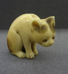 Seated cat. Japanese netsuke, made of ivory, eyes inlaid with horn, by Dosho 道笑, in Osaka-fu, 19thC
