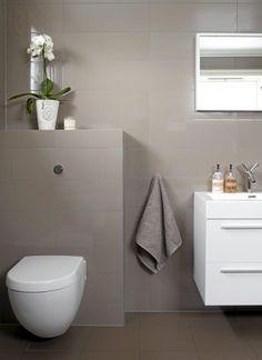 Et moderne baderom med flotte kontraster i grått og hvitt. Flisene er i en matt fargetone som skaper en rolig atmosfære.