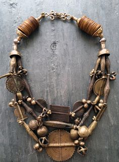 by Anna Holland | Necklace; three strands of antique brass beads, pendants, and talismans created by Akan craftsmen of the Baule tribe of the Ivory Coast, using the lost wax casting method.These are combined with rare ochre-colored antique vulcanite heishi, four bronze cones, and a bronze hook and eye clasp | 1'695$