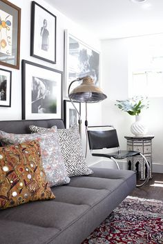 Living room with a masculine modern #eclectic vibe. Love the #light fixture, gallery wall + #cantilever chair