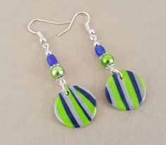 Seattle team earrings for the Seattle sports fan. 2-1/2 dangle earrings with abstract blue and green colors 5/8 disk created from polymer clay. Neon green glass beads, blue glass beads and silver bead accents. Silver hook style earrings. Clip on option available. ~ Handcrafted, one of