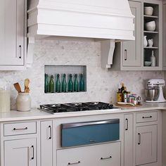 Tuck an alcove between studs and behind the range, then line it with tile to create a kitchen backsplash that doubles as storage. In this kitchen, dressed in soothing gray and blue, hexagonal marble tile and blue linear glass tile converge behind the cooktop for a one-of-a-kind backsplash idea./