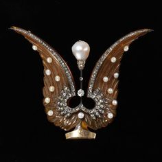 A 1900 aigrette, with horn wings and button pearls, and diamond trim, either side of a diamond pinnacle, topped with a baroque pearl. This one lives in the V & A Museum.