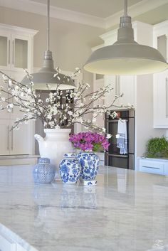 kitchen-island-styling-ideas-with-collection-of-vases-white-carrara-marble-farmhouse-pendants-chinoserie-blue-and-white-vases-3