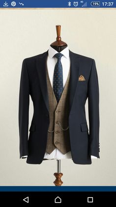 Wedding Suit Hire A mannequin wearing a navy lounge suit jacket with brown check waistcoat and patterned blue tie.A mannequin wearing a navy lounge suit jacket with brown check waistcoat and patterned blue tie. Wedding Suit Hire, Wedding Men, Wedding Suits For Groom, Tweed Wedding Suits, Groom Suits, Mens Wedding Style, Brown Suit Wedding, Vintage Wedding Suits, Wedding Suit Styles